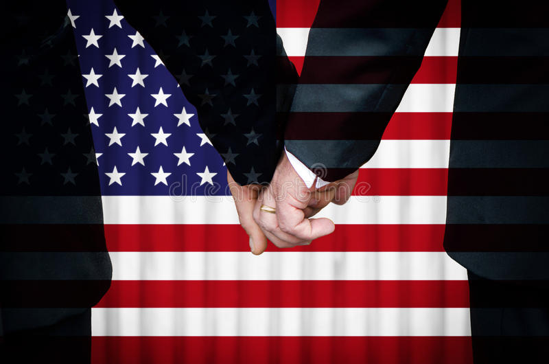 Same-Sex Marriage in the United States. Two gay men stand hand in hand before a marriage altar featuring an overlay of the flag of the United States of America stock image