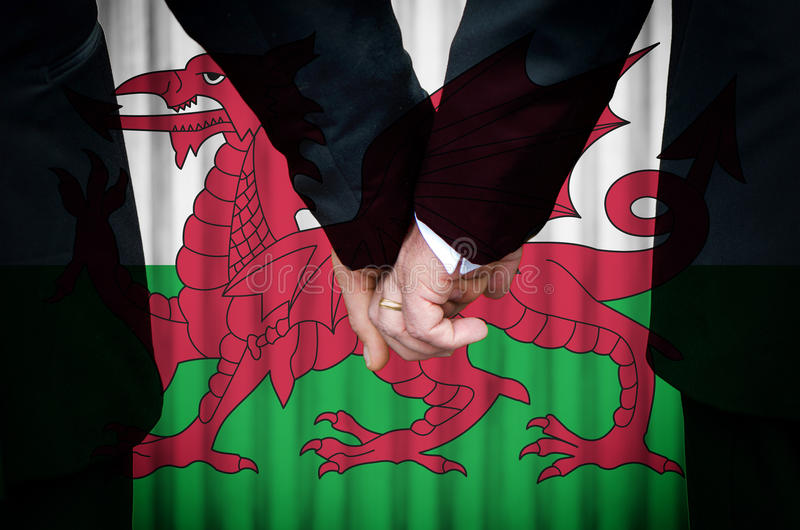 Same-Sex Marriage in Wales. Two gay men stand hand in hand before a marriage altar featuring an overlay of the flag colors of Wales, having just been legally stock photo