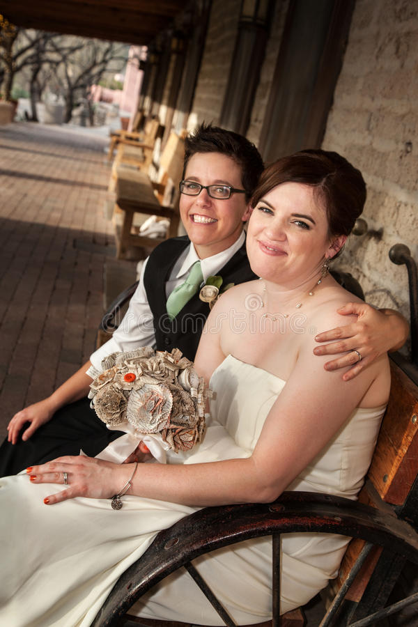 Same Sex Married Couple. Caucasian lesbian newlyweds sitting on rustic bench royalty free stock photography