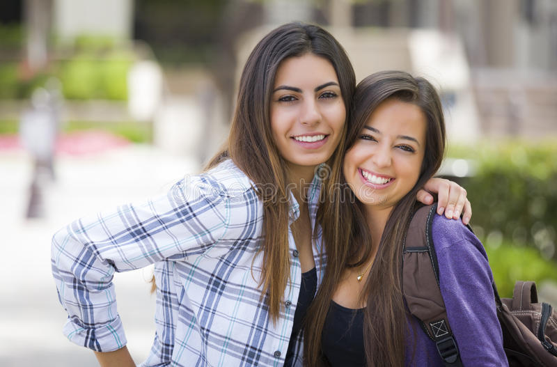 Same Sex Mixed Race Couple on School Campus. Portrait of Two Attractive Mixed Race Female Students Carrying Backpack on School Campus royalty free stock photography