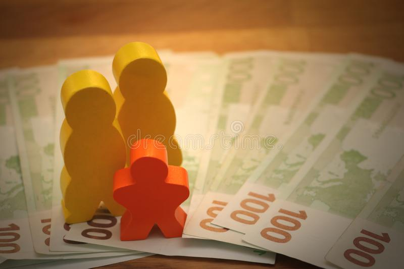 Same-sex parents with child and money euro. Symbol image, adults with child,family, same-sex parents, money, finance, toy figures royalty free stock image
