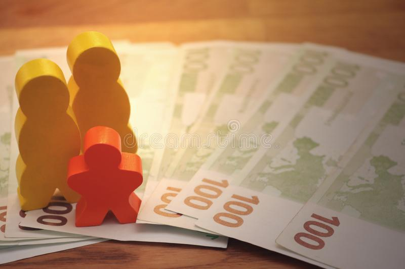 Same-sex parents with child and money euro. Symbol image, adults with child,family, same-sex parents, money, finance, toy figures stock photography