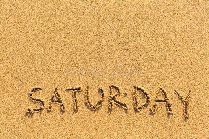 Samedi - inscription à la main sur une plage lumière-d'or photographie stock
