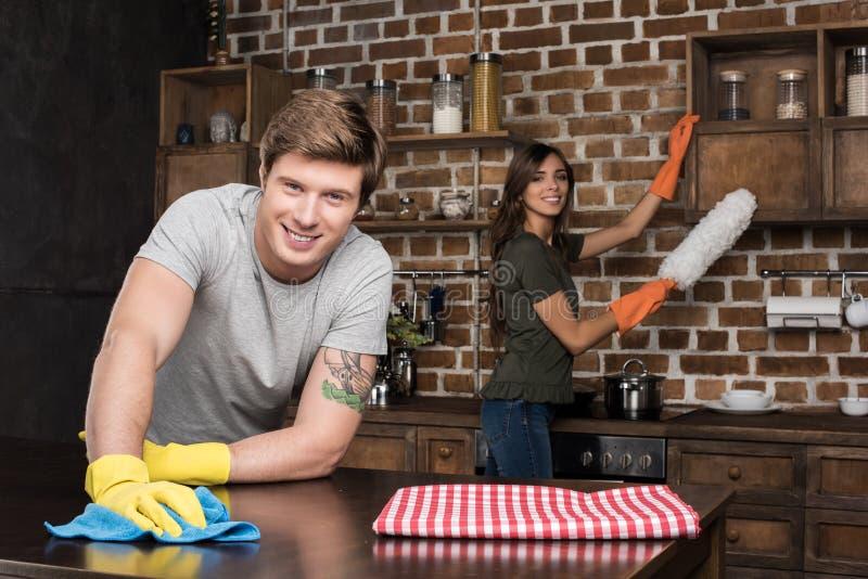 samen glimlachend jonge paar schoonmakende keuken stock foto