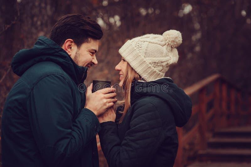 Samen het houden van van jonge paar gelukkige openlucht, het drinken thee van thermosflessen, de herfstkamp royalty-vrije stock afbeeldingen