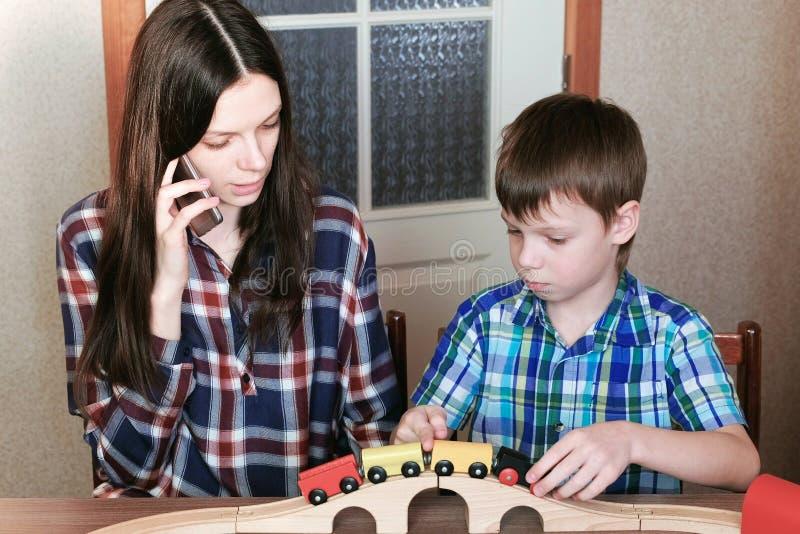 Samen het spelen De mammabespreking haar telefoon en zoon speelt een houten spoorweg met trein, wagens en tunnelzitting bij royalty-vrije stock afbeelding