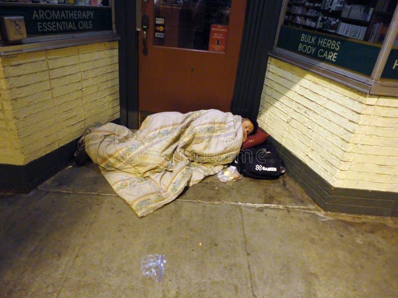 Samengebundelde dakloze persoonsslaap op deurmanier van opslag onder bl stock afbeeldingen