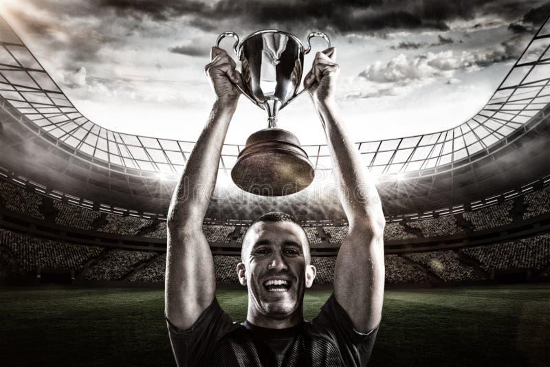 Samengesteld beeld 3D van portret van succesvolle de holdingstrofee van de rugbyspeler stock afbeeldingen