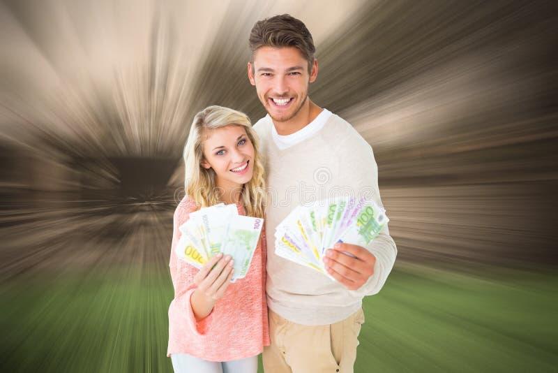 Samengesteld beeld die van aantrekkelijk paar hun contant geld opvlammen stock afbeeldingen