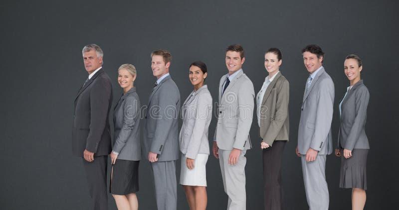 Samengesteld beeld die van commercieel team zich in rij bevinden en bij camera glimlachen royalty-vrije stock afbeelding