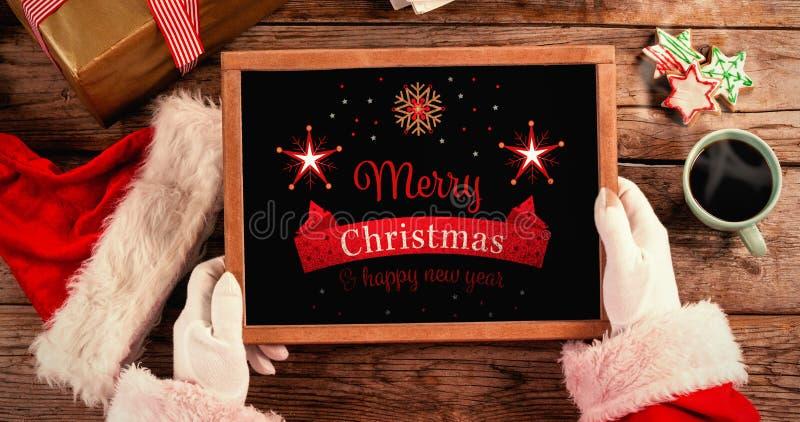Samengesteld beeld die van de Kerstman een lei met vrolijke Kerstmisteksten houden royalty-vrije stock afbeeldingen