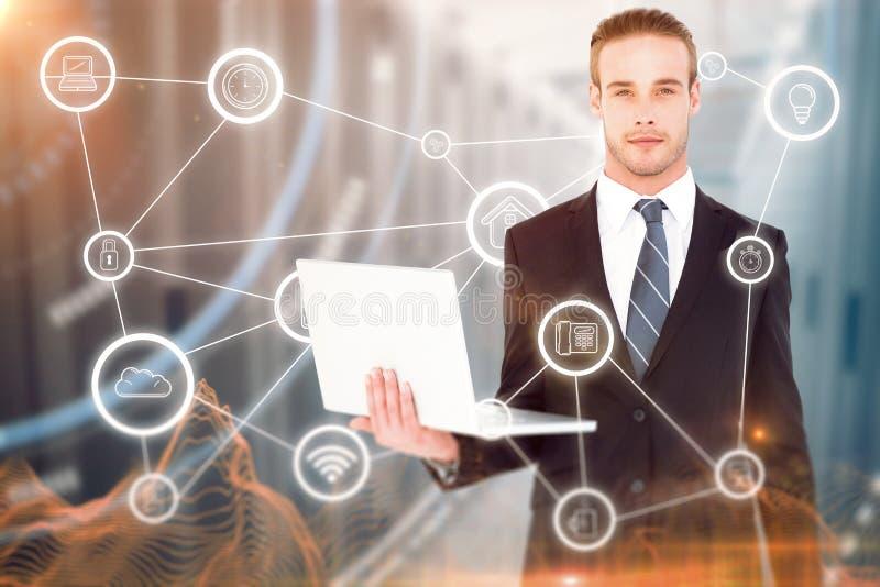 Samengesteld beeld die van ernstige zakenman en laptop stellen houden stock foto