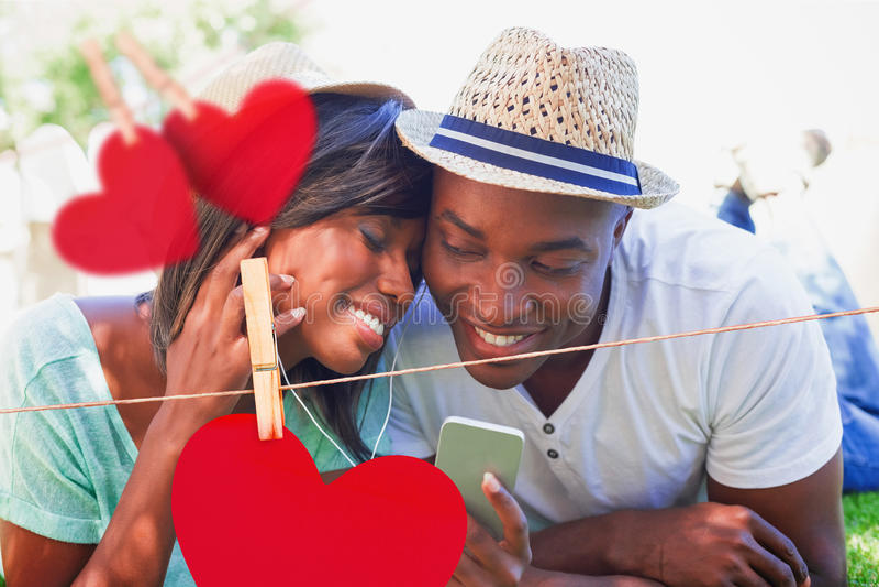 Samengesteld beeld die van gelukkig paar in tuin liggen die samen aan muziek luisteren vector illustratie