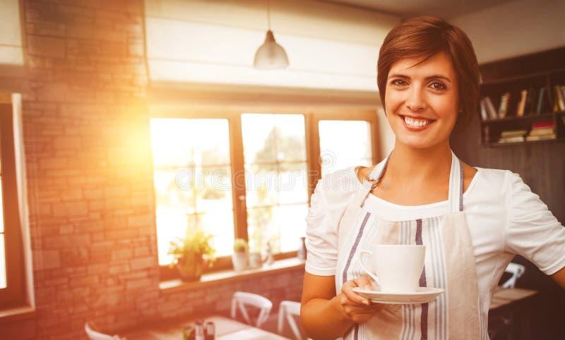 Samengesteld beeld die van glimlachende serveerster een kop van koffie houden royalty-vrije stock afbeeldingen