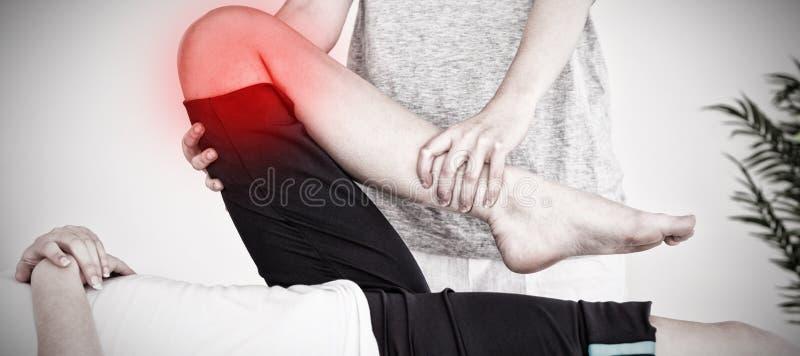 Samengesteld beeld die van masseuse het been van een younvrouw uitrekken stock afbeelding