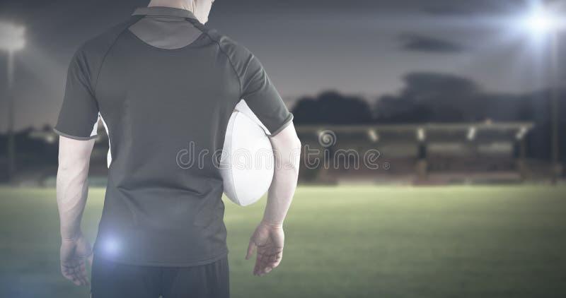 Samengesteld beeld die van rugbyspeler een rugbybal houden royalty-vrije stock foto's