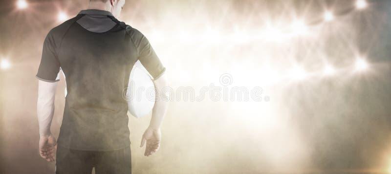 Samengesteld beeld die van rugbyspeler een rugbybal houden stock fotografie