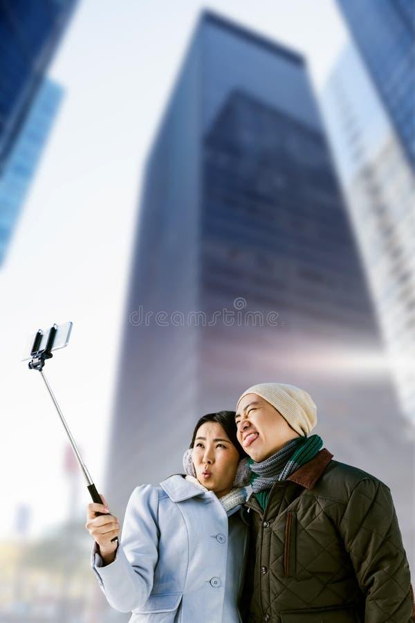 Samengesteld beeld die van speels paar selfie tegen de bouw nemen stock fotografie