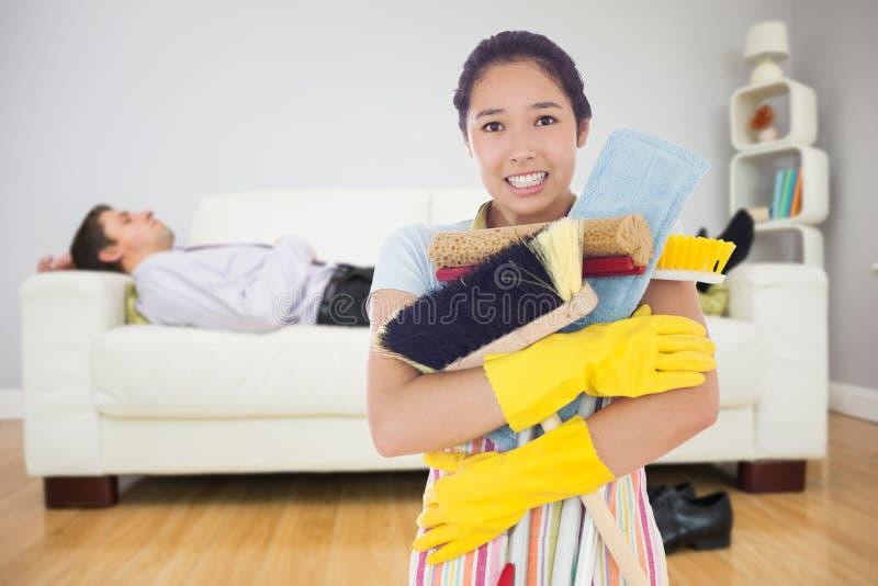Samengesteld beeld die van vrouw bijna haar schoonmakende hulpmiddelen laten vallen royalty-vrije stock foto's