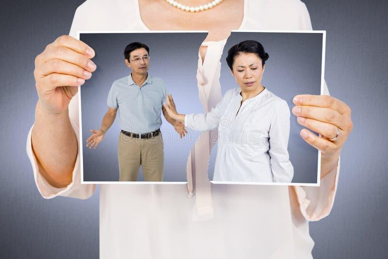 Samengesteld beeld die van vrouw een gescheurde foto houden stock foto