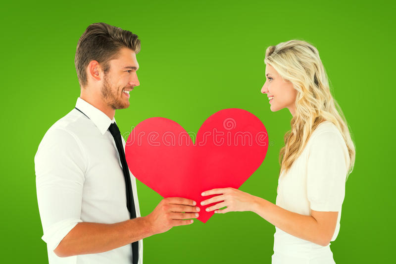 Samengesteld beeld van aantrekkelijk jong paar die rood hart houden stock afbeeldingen