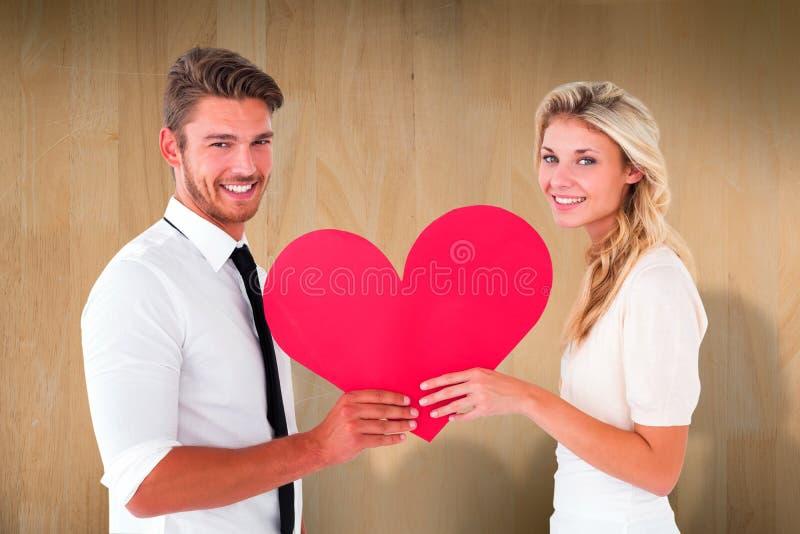 Samengesteld beeld van aantrekkelijk jong paar die rood hart houden stock fotografie