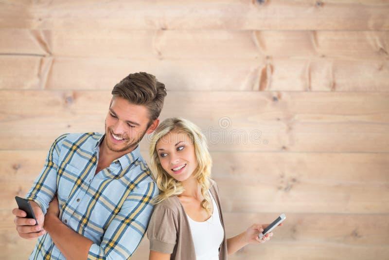 Samengesteld beeld van aantrekkelijk paar die hun smartphones gebruiken stock foto