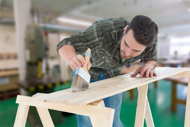 Samengesteld beeld van arbeider die borstel op houten plank gebruiken stock fotografie
