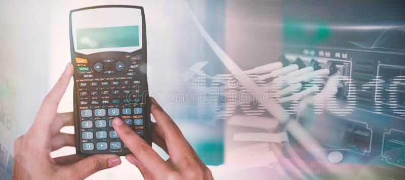 Samengesteld beeld van bebouwde handen van onderneemster die calculator gebruiken stock foto