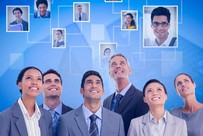 Samengesteld beeld van bedrijfsmensen die omhoog in bureau kijken stock fotografie