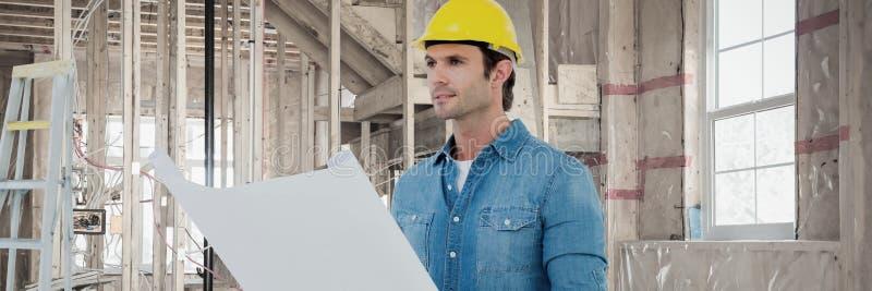 Samengesteld beeld van bouwvakker die plannen bekijken stock foto
