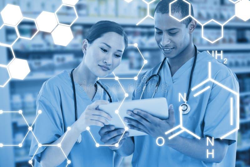 Samengesteld beeld van chirurgen die digitale tablet in het ziekenhuis bekijken stock afbeeldingen