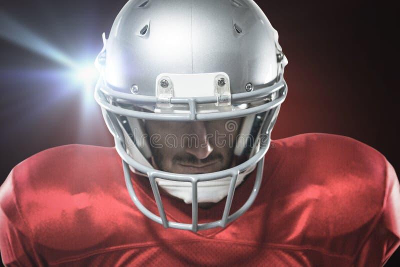 Samengesteld beeld van close-up van ernstige Amerikaanse voetbalster die in rood Jersey neer kijken royalty-vrije stock foto