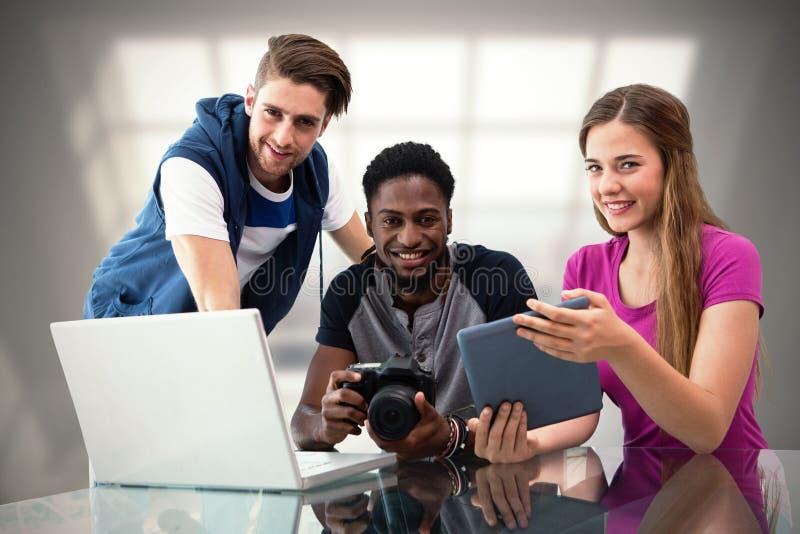Samengesteld beeld van creatief jong commercieel team die digitale tablet bekijken stock foto