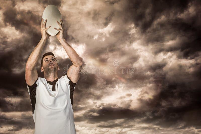 Samengesteld beeld van de bal van het de holdingsrugby van de rugbyspeler stock foto's