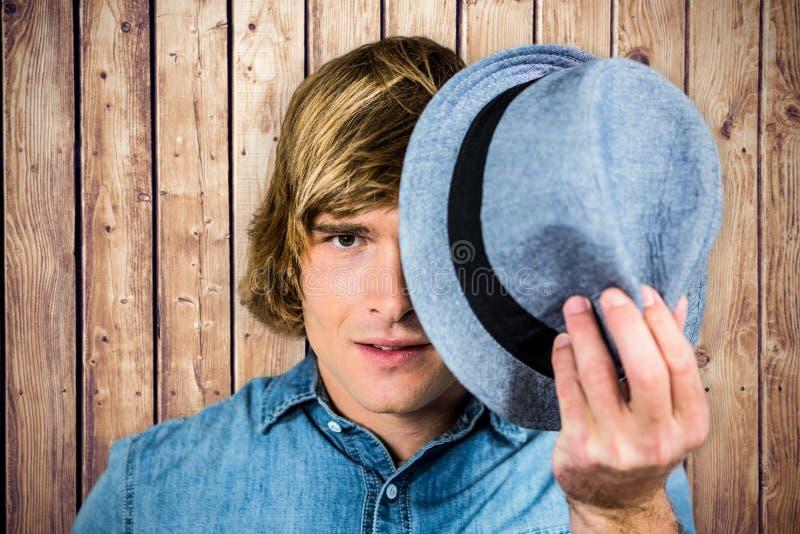 Samengesteld beeld van de geconcentreerde hipster mens die zijn gezicht verbergen stock afbeelding