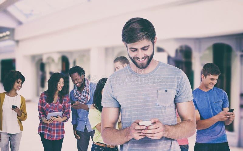 Samengesteld beeld van de glimlachende jonge mens die telefoon met behulp van royalty-vrije stock foto