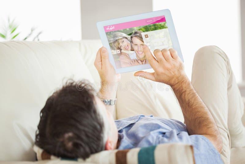 Samengesteld beeld van de mens die op bank leggen die een tabletpc met behulp van stock foto's