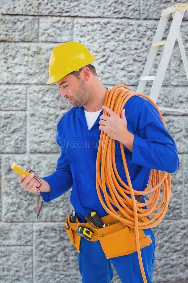 Samengesteld beeld van de multimeter van de elektricienlezing in helder bureau stock foto's