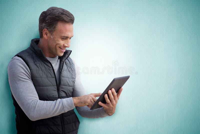 Samengesteld beeld van de rijpe mens die Internet op zijn tablet surfen royalty-vrije stock afbeeldingen