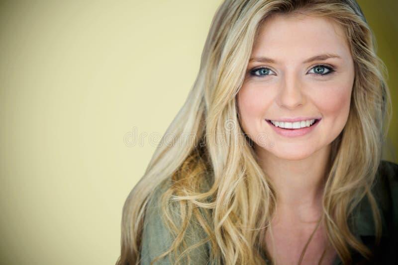 Samengesteld beeld van dicht omhooggaand portret van glimlachende jonge blondevrouw royalty-vrije stock foto's