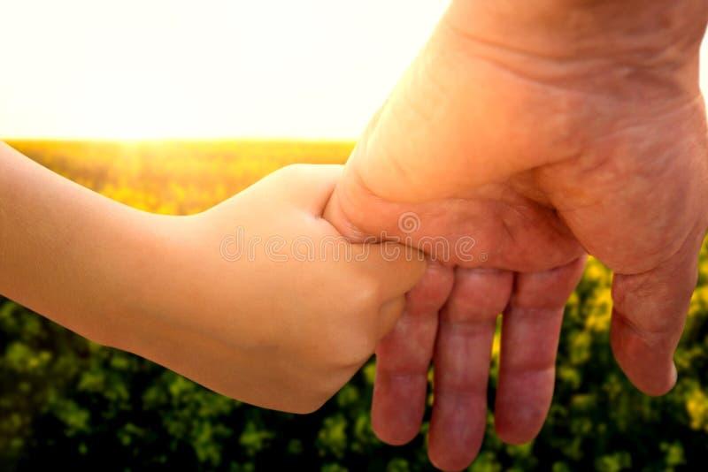 Samengesteld beeld van dichte omhooggaand van vader die zijn dochterhand houden royalty-vrije stock foto
