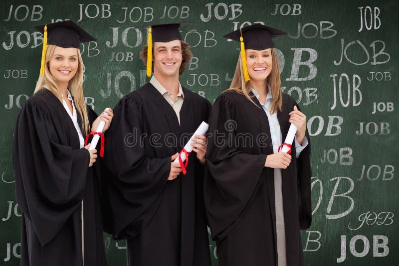 Samengesteld beeld van drie glimlachende studenten die in gediplomeerde robe een diploma houden stock foto
