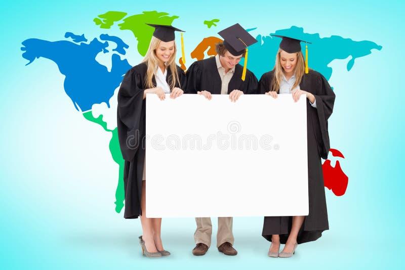 Samengesteld beeld van drie glimlachende studenten die in gediplomeerde robe een leeg teken houden stock afbeeldingen