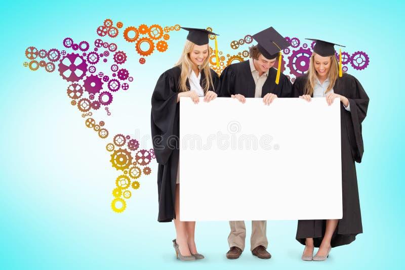 Samengesteld beeld van drie glimlachende studenten die in gediplomeerde robe een leeg teken houden royalty-vrije stock afbeeldingen