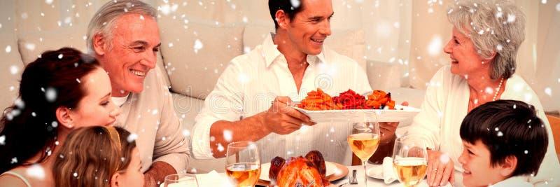 Samengesteld beeld van familie die een groot diner hebben thuis royalty-vrije stock afbeeldingen