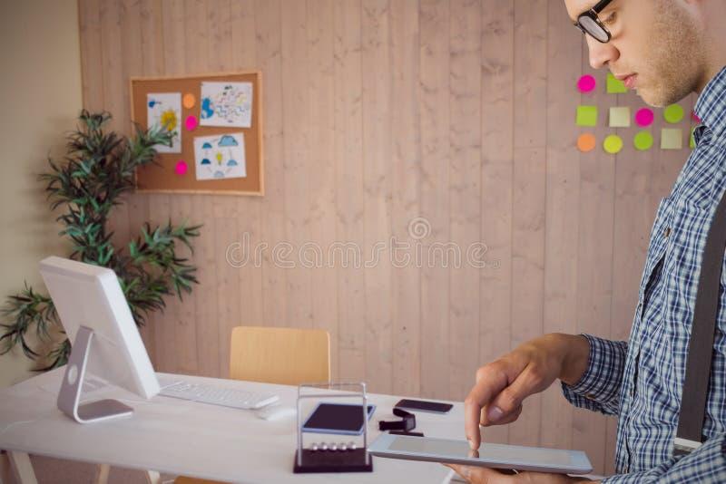 Samengesteld beeld van geeky zakenman die zijn tabletpc met behulp van stock foto