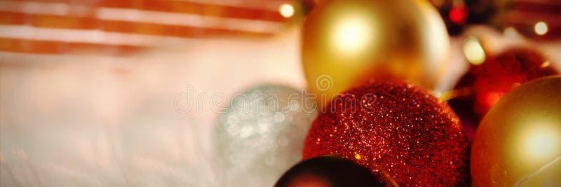 Samengesteld beeld van gekleurde Kerstmisornamenten op tapijt stock afbeelding