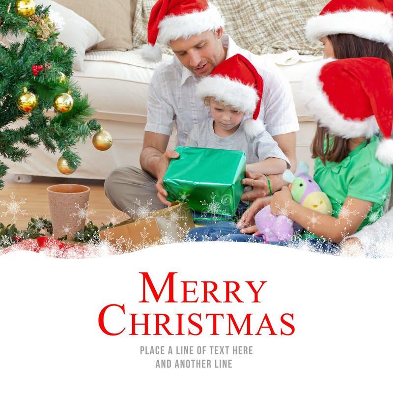Samengesteld beeld van gelukkige familie die de kleine jongen bekijken die aanwezige Kerstmis openen royalty-vrije stock fotografie