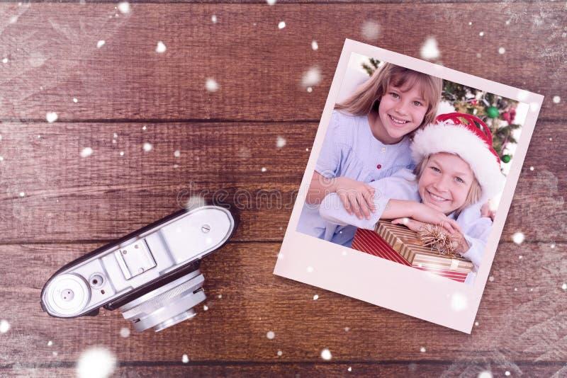 Samengesteld beeld van glimlachende siblings die Kerstmisgiften houden stock afbeeldingen